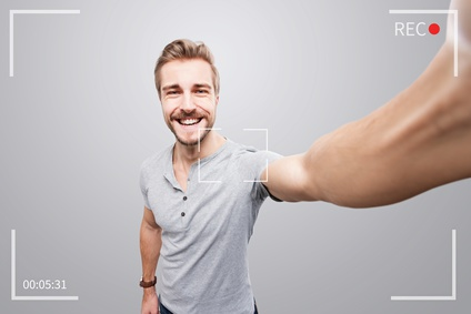 Handsome man takes a video of himself